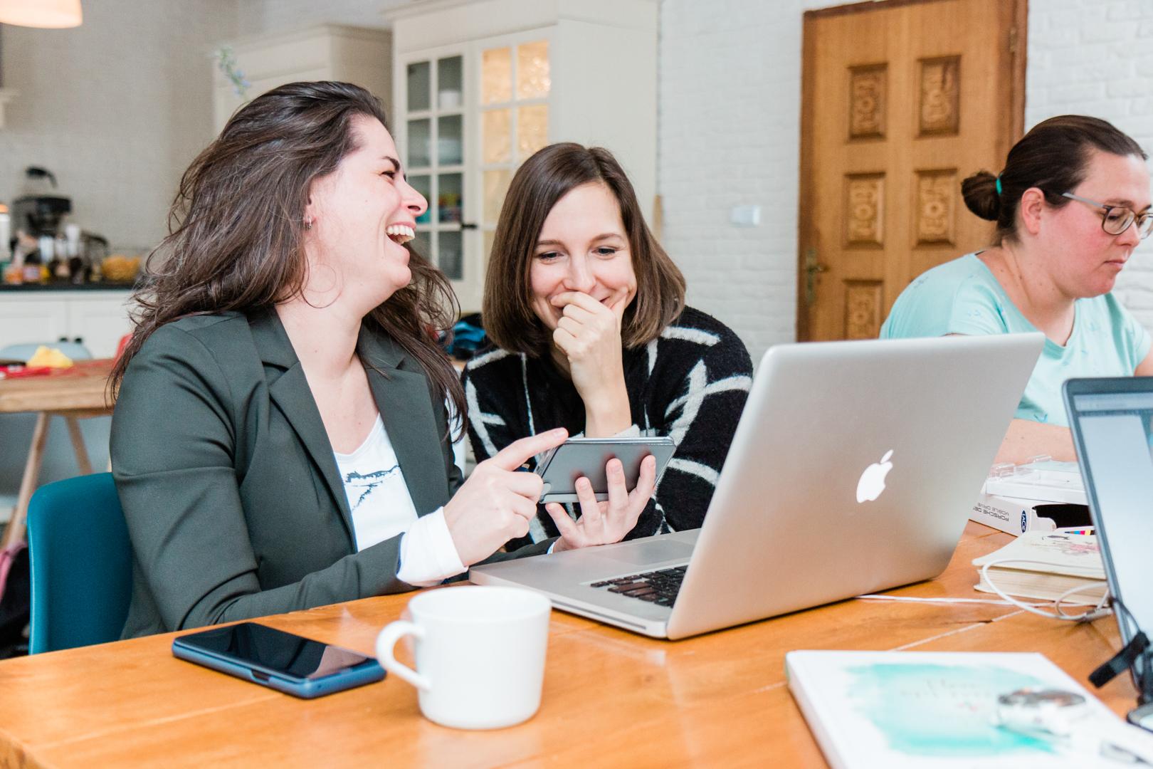 Lachende onderneemsters achter de laptop